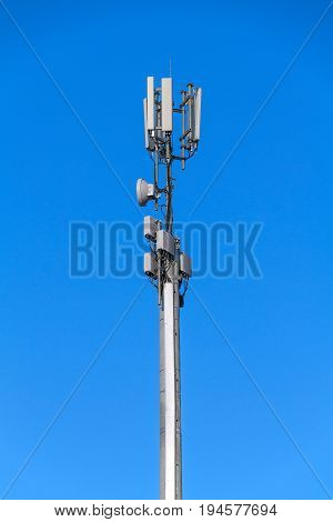 Tower with antennas of cellular communication on blue sky background
