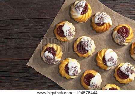 Shortbread cookie with jam and sugar icing on dark wooden table top view