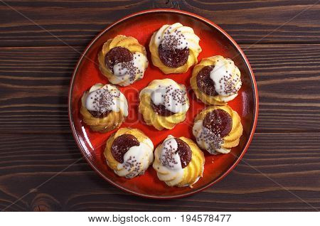Shortbread cookie with jam and sugar icing in red plate on dark wooden table top view