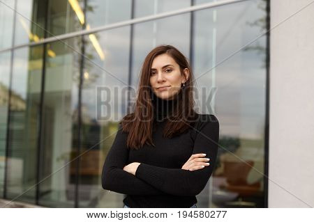 Urban street portrait of serious beautiful young European woman with long dark hair posing against glass windows office building keeping arms crossed and looking at camera with confident expression