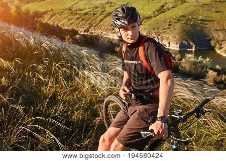 Attractive cyclist rirding mountain bike above beautiful river in the field in the countryside. Young sportsman dressed in the blck sportwear, with helmet and red backpack. Beautiful landscape like a background. Concept of the healthy lifestyle