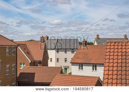 Roof top view of modern urban housing estate. Bright cloudy day over new varied homes on crowded suburban residential area.