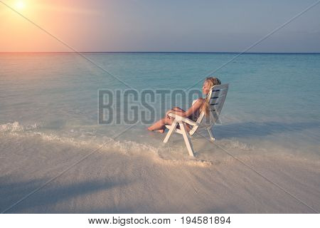 Young pretty woman tans in beach chair in sea toning