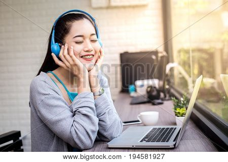 Young asian woman using blue headset for listen music with attractive smiling. Woman lifestyle concept. 20s years old.