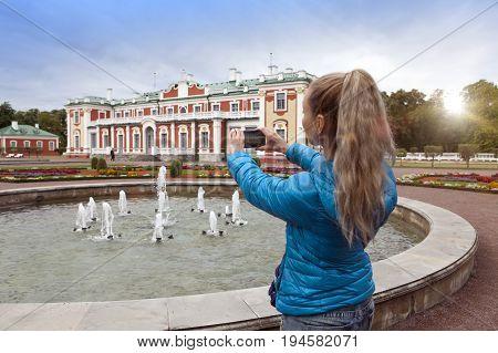 TALLINN ESTONIA- SEPTEMBER 7 2015: The woman photographs the Kardiorg palace at Kadriorg Park on phone in Tallinn Estonia.