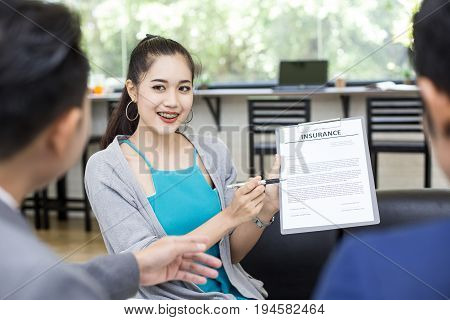 Asian woman try to present detail of insurance paper to customer at cafe. Woman in presentation concept. 20-30 years old.