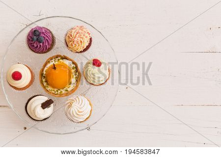 Top view on homemade vanilla blueberyy lemon chocolate cupcakes on cristal plate on white retro wooden background. Healthy food snack for birthday party or celebration
