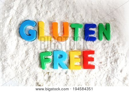 Gluten free text spelled out with colored letters in white flour