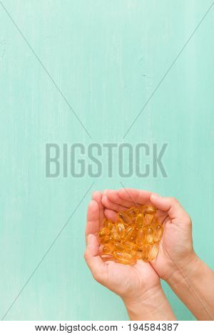 Top view on woman's hands holding pile of capsules Omega 3 on turquoise background.