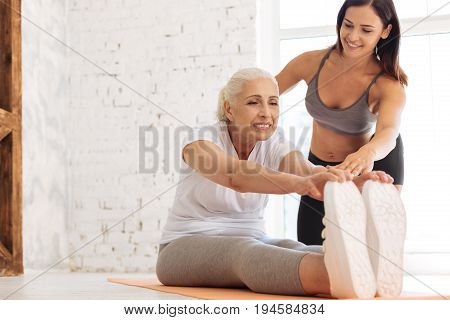 Feel this exertion. Sporty senior woman keeping smile on her face and sitting near her instructor while putting fingers on the trainers