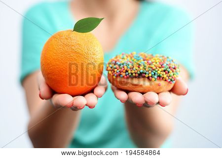 Young woman holding in hands an orange and a tasty multicolored donut, choosing healthy food or dessert
