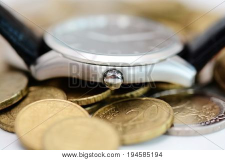 Watch on pile of coins suggesting that time is a valuable resource