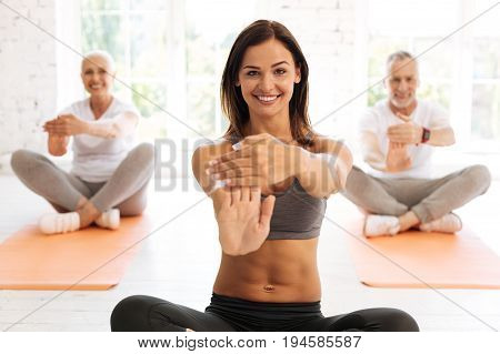 Good day. Delighted elderly people sitting on the mats keeping smile on faces while doing exercises with pleasure