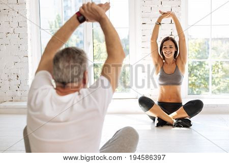 Sport for everybody. Active pensioner sitting in yoga pose and holding arms upwards while posing with back on camera