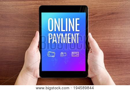 Two Hand Holding Tablet With Online Payment And Icon On Screen At Dark Brown Table Top,digital Busin