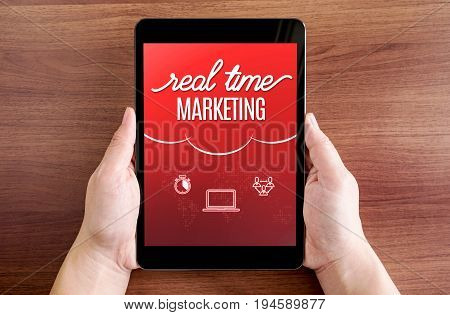 Two Hand Holding Tablet With Real Time Marketing And Icon On Screen At Dark Brown Table Top,digital