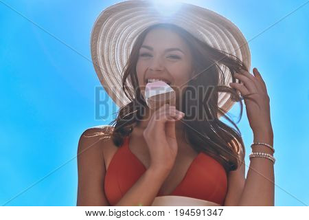 Cooling off. Low angle view of attractive young woman in swimwear eating an ice-cream while standing outdoors