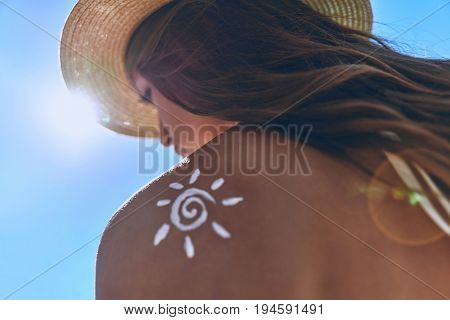 Staying safe all summer long. Low angle rear view of young woman with a suntan lotion on her shoulder sunbathing while sitting outdoors