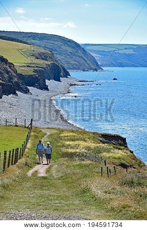 Westward Ho! North Devon England 5th July 2017 - Walkers on Cornborough Cliff walking towards the coastal town of Westward Ho! on the Southwest Coast National Trail Path.