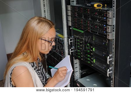 Young Woman Engineer It Between The Server Racks In The Data Center