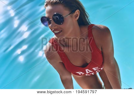 Gorgeous beauty. Top view of attractive young woman in swimwear smiling while getting out the swimming pool