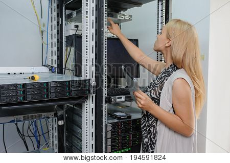 Young Woman Engineer It With Tablet Between The Server Racks