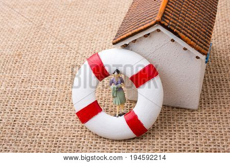 Model House And A Life Preserver With A Woman Figure