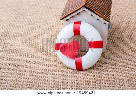 Model House And A Life Preserver With Heart Shaped