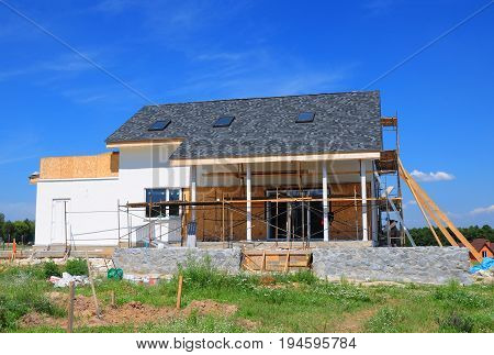 Renovate and repair residential house facade wall with mineral wool insulation plastering painting wall. House Construction with asphalt shingles roof skylights terrace patio. Attic skylight.