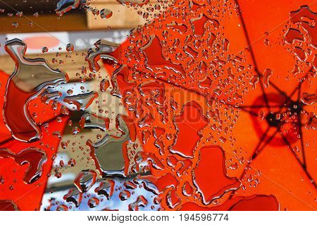 Reflection of a red umbrella on a glass table in a street city cafe on a summer day
