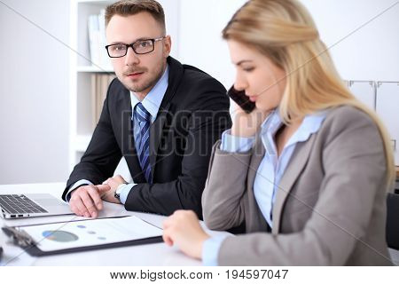 Two successful business partners working at meeting in office. Focus on blonde while talking by phone.