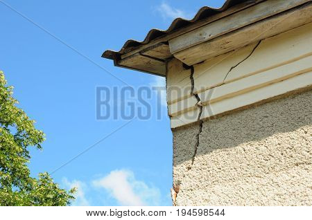 Architecture detail of damaged house corner dilapidated old building facade wall. Roof repair.