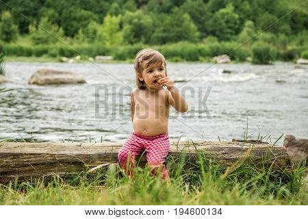 little girl sitting on a log near the river the concept of summer holiday of children