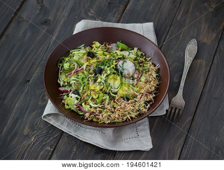 Salad from brussels sprouts with radish raisins and sprouts of wheat. Healthy diet detox food. On a wooden background in a rustic style