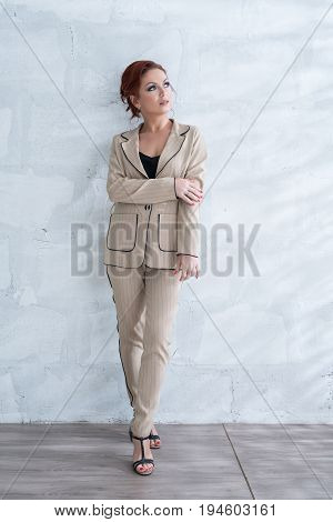 Beautiful brown haired woman in nice beige jacket and pants posing near the brick wall studio portrait