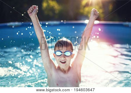 Happy little boy enjoying swimming pool in sunset hands up in the air