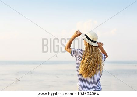 Travel woman on beach enjoying blue sea and sunset wearing white beach sun hat on summer vacation