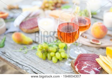 Picnic outdoor rose with wine fruits meat and cheese