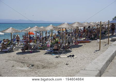 Chaniotis, Greece - July 08 2017: Bathers on the beach on a hot summer day. Sunbathers on a beach with beach umbrellas at Chalkidiki peninsula.