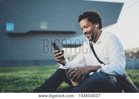Young African American man in headphone sitting at sunny city park and enjoying to listen to music on his smart phone.Blurred background