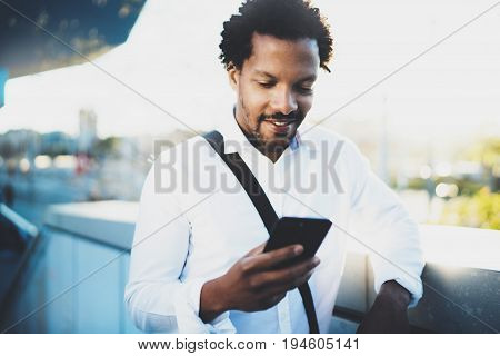 Closeup view of Happy smiling African man using smartphone outdoor.Portrait of young black cheerful man texting a sms message with friends.Blurred background