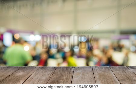 Empty Wooden Table In Front Of Blurred People In Auditorium