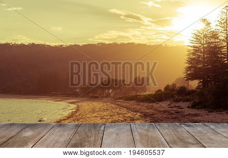 Empty Wooden Table In Front Of Calm Sunny Beach With Sunset In Background