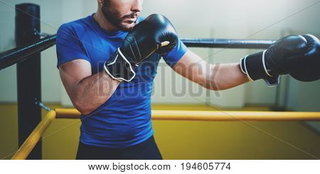 Young man boxing workout on ring in a fitness club. Caucasian male boxer in black gloves. Muscular strong man on background boxing gym.Horizontal wide