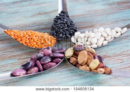Yellow Lentils, Black, White, Brown, Purple Beans On Metal Spoons