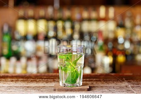 An invigorating gin-based cocktail is on the bar counter on a blurry bottle background space for text