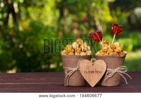 Two paper buckets with popcorn and heart shaped lollipops. Sweet hearts on a stick and sweet caramel popcorn. Romantic concept.