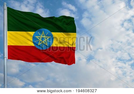 National flag of Ethiopia on a flagpole in front of blue sky.