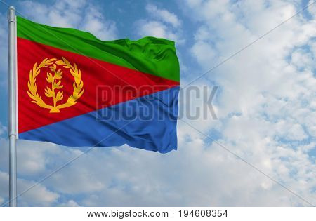 National flag of Eritrea on a flagpole in front of blue sky.