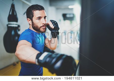 Young muscular kickboxing fighter practicing kicks with punching bag.Kick boxer boxing as exercise for the fight.Boxer hits punching bag.Concept of a healthy lifestyle.Horizontal